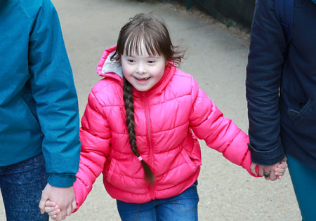 Down Syndrome girl holding the arms of her parents