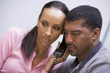 African American couple listening to news on the telephone